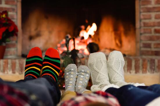 feet-in-christmas-socks-near-fireplace-relaxing-at-home-min